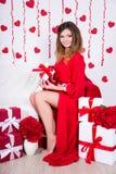 Wspaniała kobieta w czerwieni sukni obsiadaniu w dekorującym pokoju z flowe obrazy royalty free