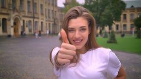 Wspaniała kobieta z długim lekkim włosy pokazuje jak gest i patrzeje kamerę gwarantującą