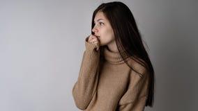 Wspaniała młoda brunetki kobieta w ciepłym trykotowym pulowerze na jasnopopielatym tle obrazy stock