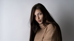 Wspaniała młoda brunetki kobieta w ciepłym trykotowym pulowerze na jasnopopielatym tle zdjęcie royalty free