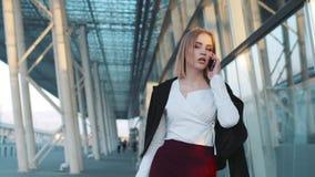 Wspaniała młoda kobieta ciągnie jej bagaż i opowiada na telefonie Być w lotnisku aktywny tryb życia zbiory