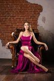Wspaniała młoda kobieta w luksusowej sukni a siedzi w krześle w luksusowym mieszkaniu zdjęcia royalty free