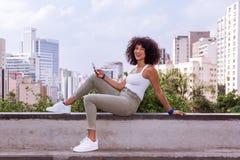 Wspaniała młoda kobieta z afro fryzury obsiadaniem i używać komórka zdjęcia stock