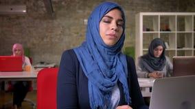 Wspaniała muzułmańska kobieta jest siedząca i pisać na maszynie na jej laptopie z pracującymi arabskimi kobietami na tle, prosty