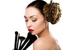 Wspaniała naga młoda kobieta z złotym kwiatem w włosianym mienia makeup szczotkuje Zdjęcie Royalty Free