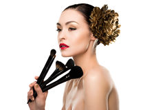 Wspaniała naga młoda kobieta z złotym kwiatem w włosianym mienia makeup szczotkuje Obraz Royalty Free