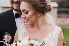 Wspaniała panna młoda z nowożytnym bukietem i eleganckim fornala delikatnie hugg fotografia royalty free