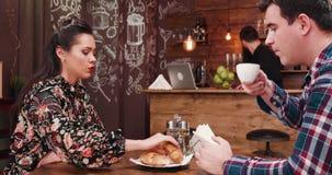 Wspaniała para pije kawę i je croissants w eleganckiej modnisia sklepu z kawą pubu restauracji zdjęcie wideo