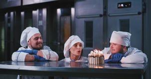 Wspaniała piekarniana dziewczyna jest ubranym szefa kuchni ubiór robi życzeniu i dmucha za świeczkach na torcie, ona wtedy oklask zdjęcie wideo