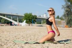 Wspaniała sprawności fizycznej dziewczyna w okularach przeciwsłonecznych rozciąga przy plażą przed trenować Opróżnia przestrzeń obrazy royalty free