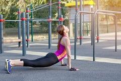 Wspaniała szczupła młoda kobieta ćwiczy joga przy plenerowym sportsground Kobry asana Calmness i relaksuje, rozciągający Prawdziw fotografia royalty free