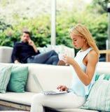 Wspaniała zamożna kobieta cieszy się filiżankę kawy podczas gdy siedzący w nowożytnej restauracyjnej kanapie Zdjęcia Royalty Free
