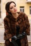 Wspaniała zmysłowa kobieta z ciemnym włosy w luksusowym futerkowym żakiecie i rzemiennych rękawiczkach zdjęcia stock