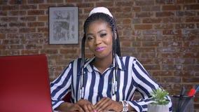 Wspaniałego afrykańskiego smiley żeński obsiadanie przy jej miejscem pracy i ono uśmiecha się przy kamerą