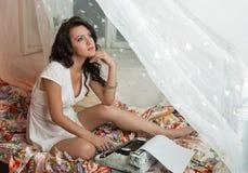 Wspaniałej młodej brunetki pisarski obsiadanie na łóżku Fotografia Stock