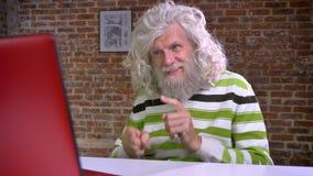 Wspaniały caucasian dziad z biel długą brodą i włosy bawić się bębeny z palcami i tanem podczas gdy siedzący i