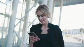 Wspaniały Europejski bizneswoman z formalną fryzurą w pośpiechu przechodzi lotniskowego terminal, teksty wiadomość na ona zdjęcie wideo