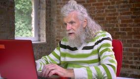 Wspaniały kosmaty starzejący się caucasian mężczyzna z długą białą brodą jest pisać na maszynie wygranego gest z jego pięścią i d
