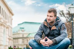 Wspaniały młody człowiek pozuje przed starymi budynkami obrazy stock