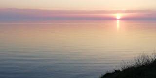 Wspaniały menchii i bzu zmierzch nad spokojną rozległością morze fotografia royalty free