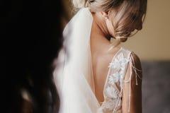 Wspaniały piękny panny młodej kładzenie na eleganckiej ślubnej sukni przy wygraną zdjęcie royalty free