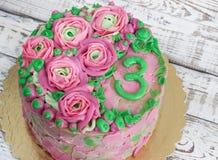 Wspaniały tort zakrywający w różach robić masła kremowy lodowacenie na białym drewnianym tle Zdjęcie Stock