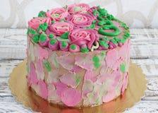 Wspaniały tort zakrywający w różach robić masła kremowy lodowacenie na białym drewnianym tle Obrazy Stock