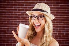 Wspaniały uśmiechnięty blondynka modniś przedstawia oddaloną filiżankę Zdjęcia Royalty Free