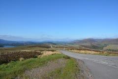 Wspaniały widok średniogórza z górami, jezioro, ulica i niebo Fotografia Stock