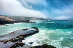 Wspaniały widok przy mglistą skalistą plażą Obraz Stock
