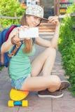 Wspaniała deskorolkarz dziewczyna robi selfie na telefonie komórkowym Zdjęcie Stock