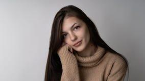 Wspaniała młoda brunetki kobieta w ciepłym trykotowym pulowerze na jasnopopielatym tle zdjęcia royalty free