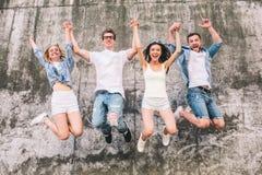 Wspaniali i ładni ludzie są skakać w powietrzu Trzymają ich ręki w powietrzu zbyt Firma jest na obraz royalty free