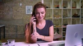 Wspaniali miedzianowłosi caucasian kobiet iis wiesza nad telefonem i odpowiada spokojnie podczas gdy siedzący nera laptop ain now