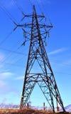 Wspiera wysokonapięciowe linie energetyczne przeciw błękitnym wiosny fabryki i nieba kominom Obrazy Royalty Free