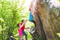 Wspinać się w naturze Przyjaciel wspinaczka kamień Dziewczyna wspina się na kamieniu, i przyjaciele wspierają ona Bouldering w na fotografia stock