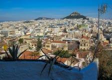Wspina się Lycabettus otaczającego białymi budynków architektura, góry, drzew, niebieskiego nieba i aloesu roślinami na akropol ś obrazy royalty free