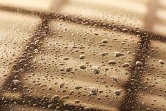 Wässern Sie Tropfen einer glänzenden metallischen Oberfläche mit Tabelle bezüglich Lizenzfreies Stockbild