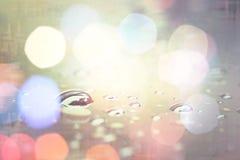 Wässern Sie Tropfen mit hellem bokeh, abstrakter Hintergrund der Regenzeit Stockbild