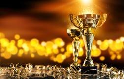 Wstawia się złotego trofeum na drewno stole z punktów światłami na tle Zdjęcia Stock
