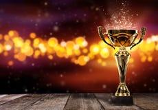 Wstawia się złotego trofeum na drewno stole z punktów światłami na tle Obrazy Stock
