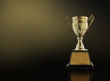 wstawia się złotego trofeum na nowożytnym czarnym tle z złocistym ligh Fotografia Royalty Free
