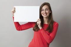 Wstrząśnięta 20s dziewczyna cieszy się robić reklamie w wystawiać pustą wszywkę Zdjęcia Royalty Free