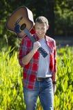 Wstrząśnięta 40s mężczyzna mienia gitara w parku dla muzyki outdoors Obraz Royalty Free