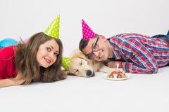 Wszystkiego najlepszego z okazji urodzin pies z rodziną w urodzinowych kapeluszach fotografia royalty free