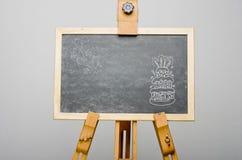 Wszystkiego najlepszego z okazji urodzin pisać na urodzinowym torcie z świeczkami na wierzchołku, na czarnym chalkboard, sztaluga obraz stock