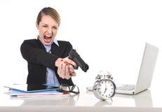 Wütende verärgerte Geschäftsfrau, die Gewehr auf Wecker im Konzept unzeitgemäß zeigend arbeitet Lizenzfreies Stockfoto