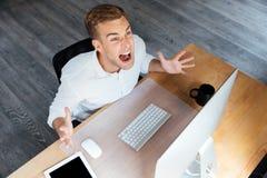 Wütender gereizter junger Geschäftsmann, der mit Computer und dem Schreien arbeitet Stockfotos