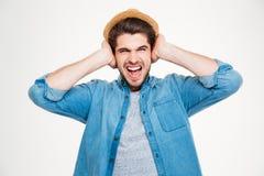 Wütender gereizter junger Mann bedeckte Ohren, indem er Hand und schrie Stockbild