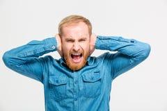Wütender hysterischer Mann schloss Ohren, indem er Hand und schrie Stockbilder
